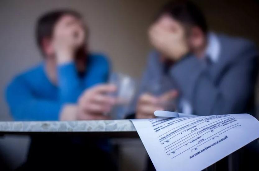 Фото мошенники по сделкам с недвижимостью - черные риэлторы сговариваются над договором купли-продажи квартиры.