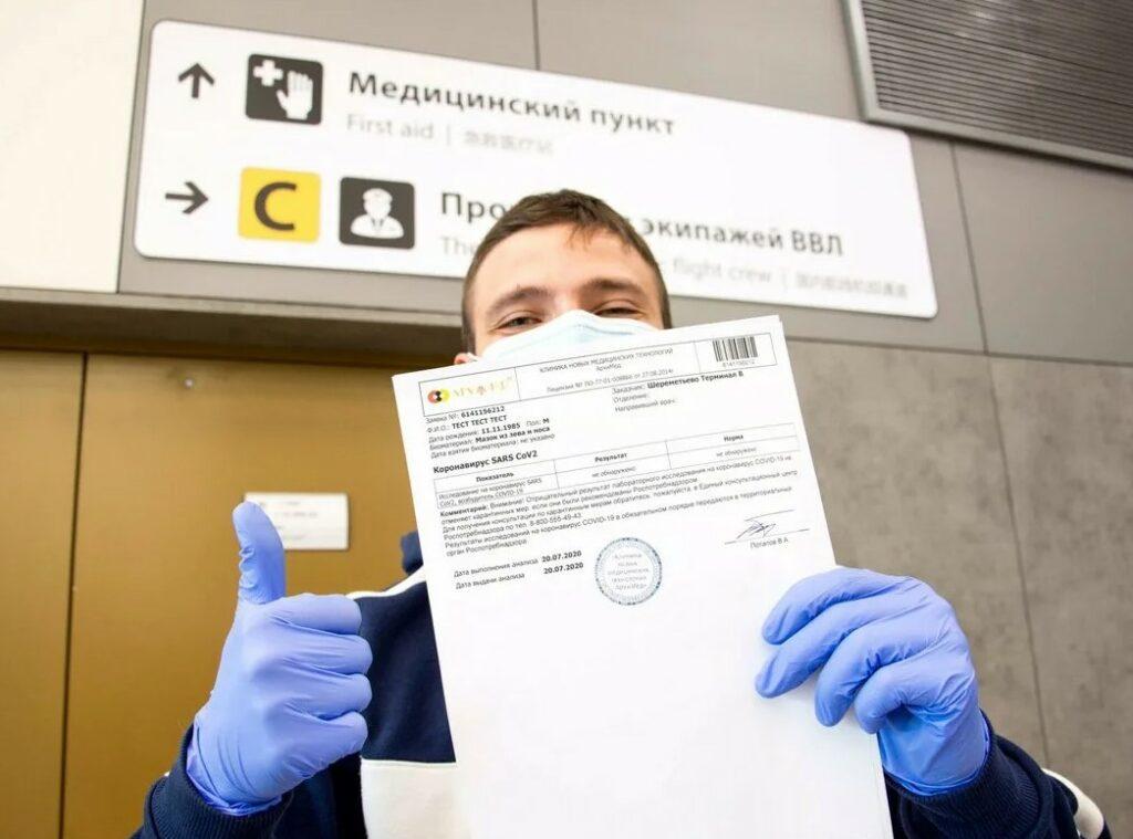 На фото молодой человек после посещения мед. пункта показывает тест на Ковид с отрицательным результатом на коронавирус.