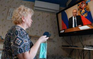 На фото женщина смотрит по ТВ каналу Вести 24 выступление президента Путина об оказании финансовой помощи малообеспеченным семьям.