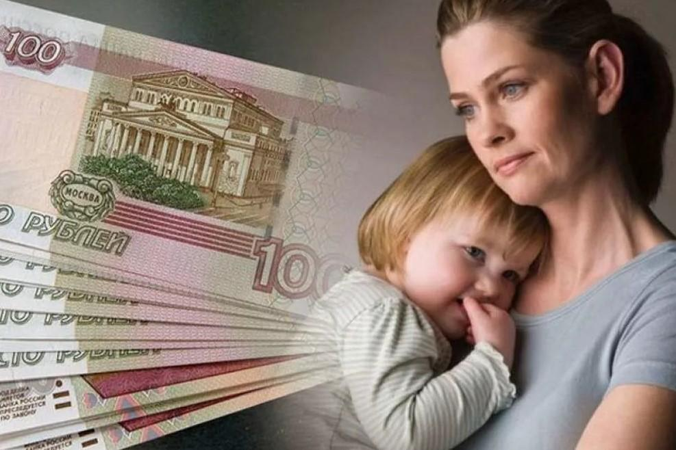 На фото молодая женщина с маленьким ребенком на руках желающая оформить получение детского пособия за рождение ребёнка.